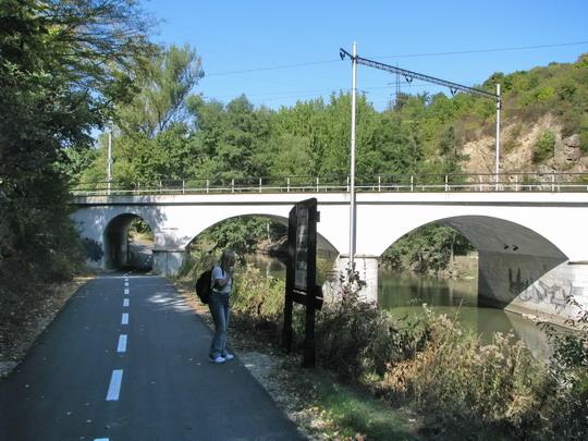 Helena zkoumá moudra na tabuli u cyklostezky, v pozadí most u tunelu Blanenský 1 © PhDr. Zbyněk Zlinský