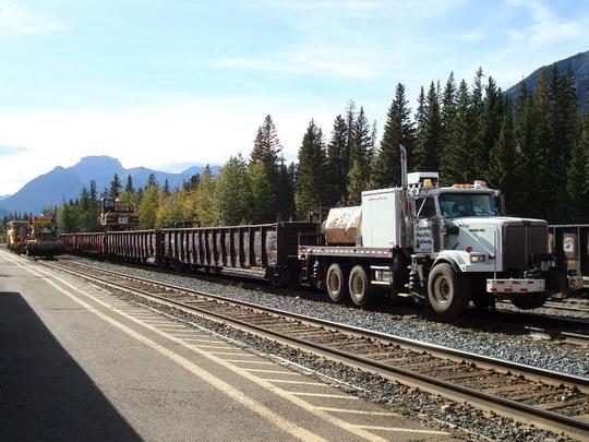 21.9.2009 - Banff, AB. Vlak na zber starých podvalov ťahaný dvojcestným nákladiakom križuje pracovné stroje © Michal Stríž