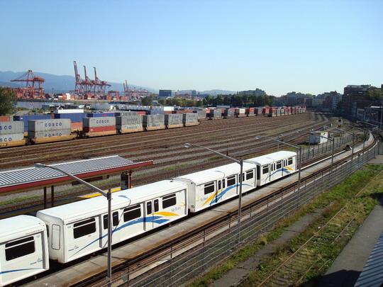 """27.9.2009 - Vancouver, BC. Súprava dvoch dvojvozňových jednotiek """"SkyTrain"""". V pozadí severný kontajnerový prístav s príslušnými vozňami © Michal Stríž"""