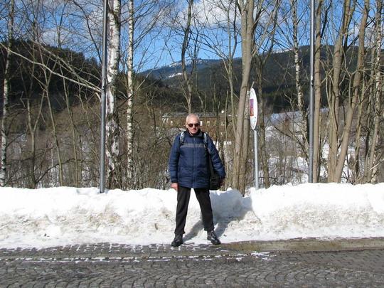 Autor stojící na hraniční čáře, vyznačené před nádražím dlažbou, pravou nohou v SRN, levou v ČR © Helena Bažantová