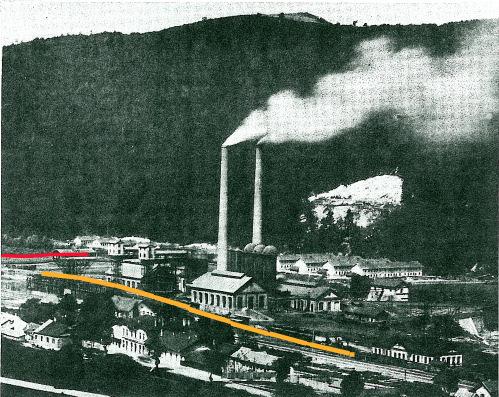 Pohled na železárny se zvýrazněným nájezdem na výsypku. U stejného zásobníku, ale ve větší výšce končila také lanová dráha zvýrazněná červeně.
