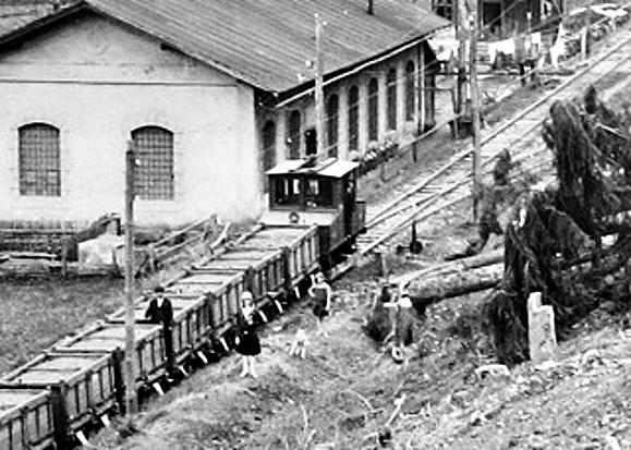 Lokomotíva AEG (smerujúca do Bindtu) odfotená s vozňami pri akumulátorovni v Markušovskej doline počas prevádzky v roku 1925 (ŠUBA Banská Štiavnica)